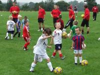 Young children participate in a game of football